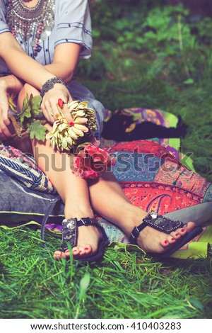 summer boho style fashion woman sit in garden holding silk flowers in hands closeup - stock photo