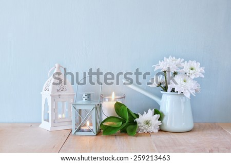 summer bouquet of flowers and vintage lantern on wooden table with mint background. vintage filtered image - stock photo