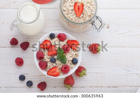 Summer breakfast. Ingredients for healthy breakfast - berries, fruit and muesli on white wooden table, close-up top view horizontal. - stock photo