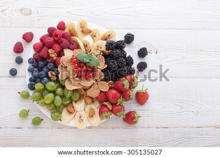 Summer breakfast. Ingredients for healthy breakfast - berries, fruit and muesli on white wooden table, close-up top view horizontal. Macro shot selective focus - stock photo