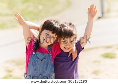 summer, childhood, family, friendship and people concept - two happy kids hugging outdoors - stock photo