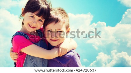 summer, childhood, family, friendship and people concept - two happy kids hugging over blue sky with clouds background - stock photo