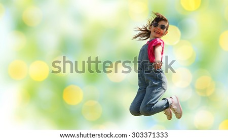 summer, childhood, leisure and people concept - happy little girl jumping high over green summer lights background - stock photo