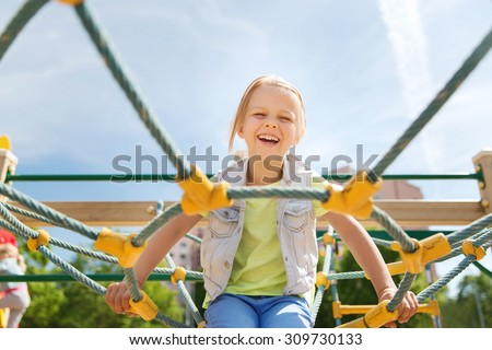 summer, childhood, leisure and people concept - happy little girl on children playground climbing frame - stock photo