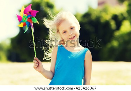 summer, childhood, leisure and people concept - happy little girl with colorful pinwheel toy outdoors - stock photo