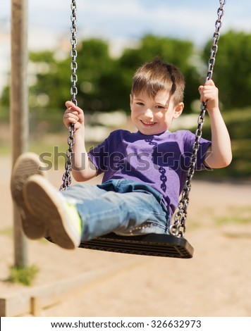 summer, childhood, leisure, friendship and people concept - happy little boy swinging on swing at children playground - stock photo