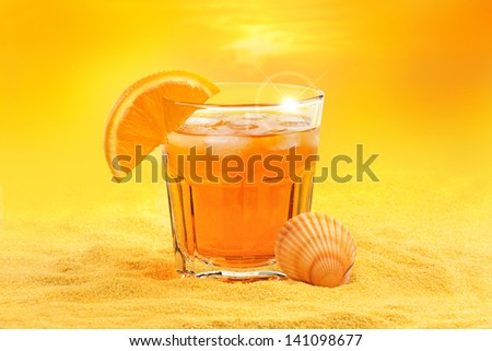 summer cocktail and scallop shell on the beach at sunset - stock photo