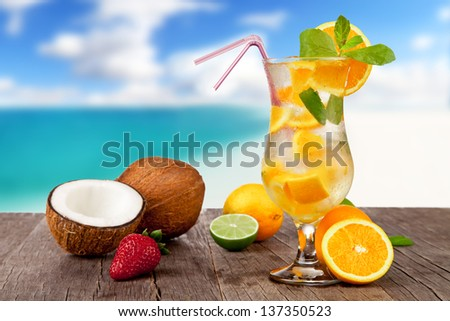 Summer cocktail with pieces of fruit on wooden table. Blur beach on background - stock photo