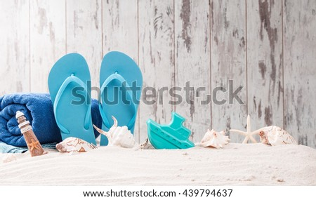 Summer concept, flip-flops, summer accessories in sand with wooden background - stock photo