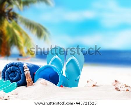 Summer concept, flip-flops, summer accessories on summer beach - stock photo