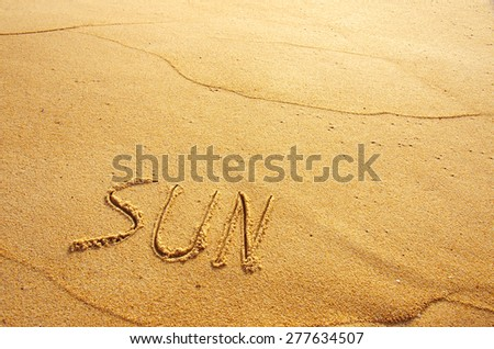 Summer concept of beach with word sun written on the sand - stock photo