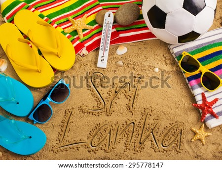 Summer concept of sandy beach, colorful flip flop shoes, sunglasses, ball and inscription - stock photo