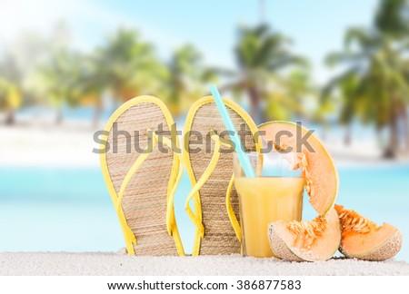 Summer concept of sandy beach, flip flops and starfish - stock photo