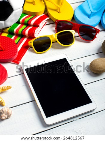 Summer concept of tablet pc, flip flop shoes, sunglasses on pier near hotel pool - stock photo