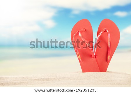 Summer concept with sandy beach and red sandals - stock photo