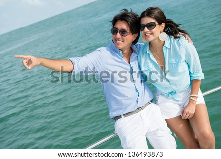 Summer couple sailing in a yacht and pointing away - stock photo