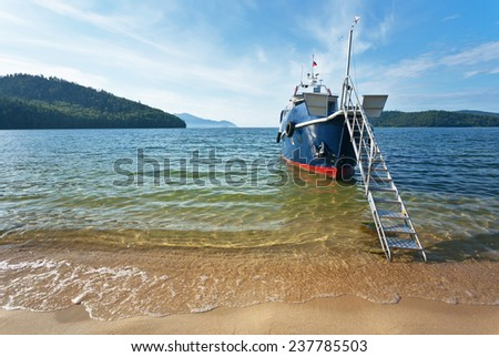 Summer cruises on Lake Baikal. Boat moored to the sandy beach in the beautiful Bay  - stock photo