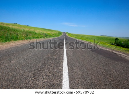 Summer day and the asphalt road in a field - stock photo