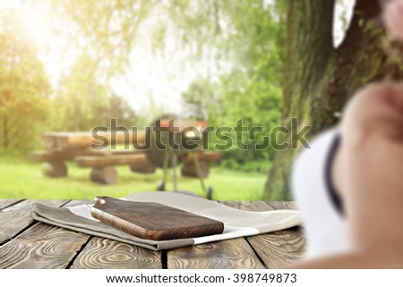 summer day in garden and woman and dark kitchen desk space  - stock photo