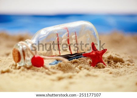 Summer days. Marine composition of beautiful sailing ship in the bottle surrounded by sea stars and seashells  in summer travelling concept  - stock photo