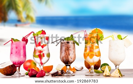 Summer drinks with blur, tropical beach on wooden table - stock photo