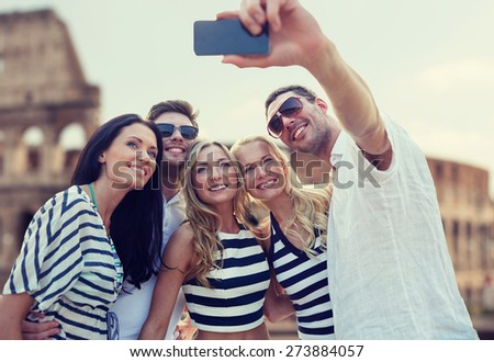 summer, europe, tourism, technology and people concept - group of smiling friends taking selfie with smartphone over coliseum background - stock photo