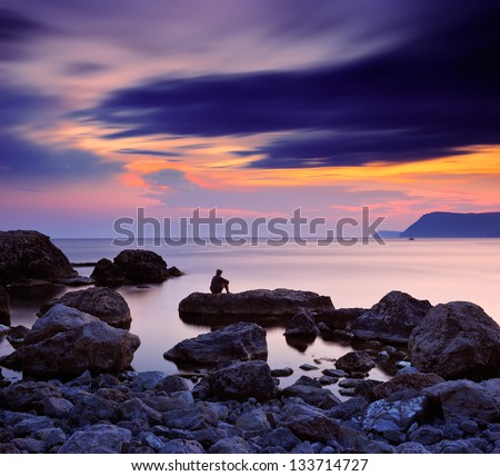 Summer evening by the sea. Mister sitting on a rock and watching the sunset at the sea - stock photo