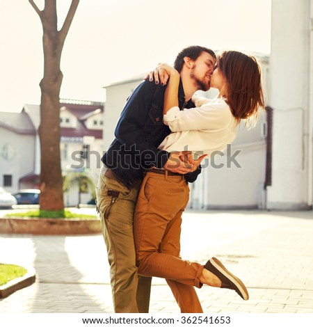 Summer evening portrait of pretty young stylish hipster couple posing and kissing outdoor on the street in spring  - stock photo