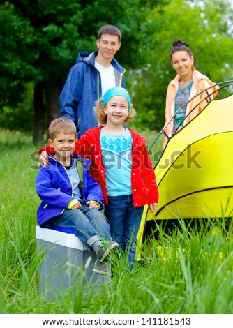 Summer, family camping - lovely sister and brother with parents near camp tent. Vertical view - stock photo
