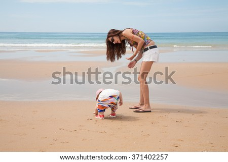 summer family of two years old baby white shirt and colorful trousers with woman mother or babysitter white jeans shorts looking for, picking and collecting sea shells at golden sand beach seaside  - stock photo