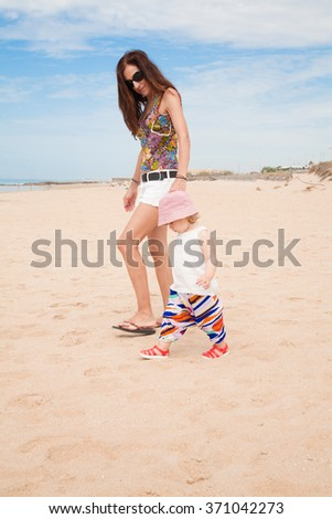 summer family of two years old blonde baby with pink hat white shirt and colorful trousers holding hand with brunette woman mother white jeans shorts walking at beach sand in Cadiz Andalusia Spain - stock photo