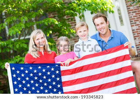 Summer: Family Posing Outdoors With American Flag - stock photo
