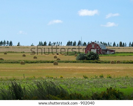 Summer farm fields with the classic red barn and hay bales. - stock photo