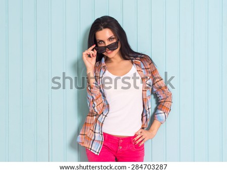 Summer, fashion and people concept -  brunette in shirt posing in sunglasses against colorful wall background in the city, beautiful young girl smiles sweetly, copy space, street fashion photo. - stock photo