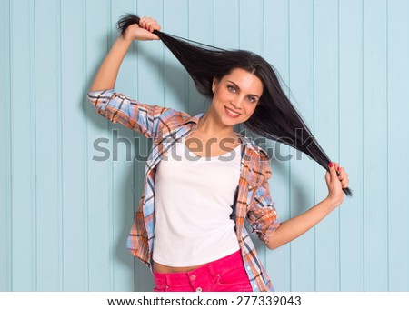 Summer, fashion and people concept -  stylish pretty brunette in shirt playful, cheerful, fooling around, posing against colorful wall backgroun,  keeps hair in the hands, copy space, photo. - stock photo