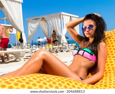 Summer fashion photo of beautiful tanned woman with brunette hair in sexy bikini relaxing at luxury beach resort on yellow beach chair. Summer close up of slim sexy woman having sunbath on vacation. - stock photo