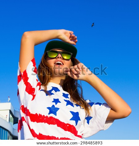 Summer fashion portrait of young teen girl having fun go crazy, wearing trendy top with american flag print,hat, hipster mirrored glasses. Sitting on the terrace with amazing sea view. Joy Sea Sunset - stock photo