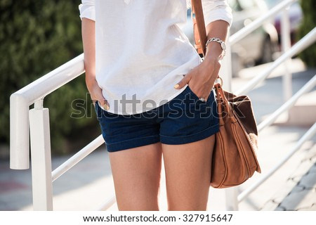 summer fashion woman in white shirt and shorts  stand by  fence, outdoor shot,  summer day, closeup - stock photo