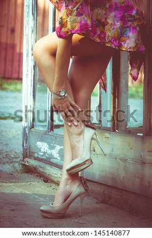 summer fashion woman with long slim legs in high heel shoes against old door with glass  outdoor shot retro colors - stock photo
