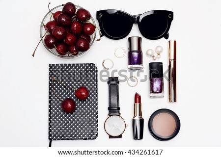 Summer flat lay photography essential accessories for woman. Overhead view of female beauty items : cosmetics, sunglasses, notebook, lipstick, nail polish and cherry - stock photo
