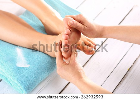 Summer foot care. Woman in a beauty salon for pedicure and foot massage. - stock photo