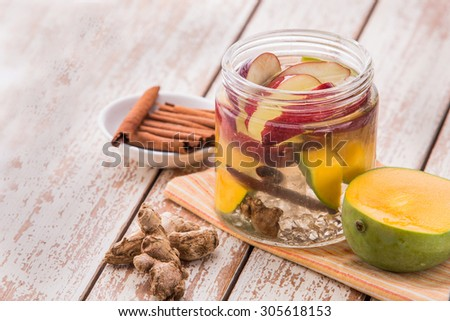Summer fresh fruit Flavored infused water mix of apple, mango, ginger and cinnamon - stock photo