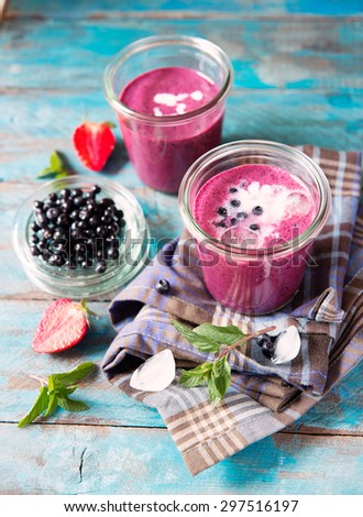 summer fruits smoothie in a glass on the blue rustic table table with mint and ice cube - stock photo