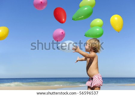 Summer fun: Child with ballons on the beach - stock photo
