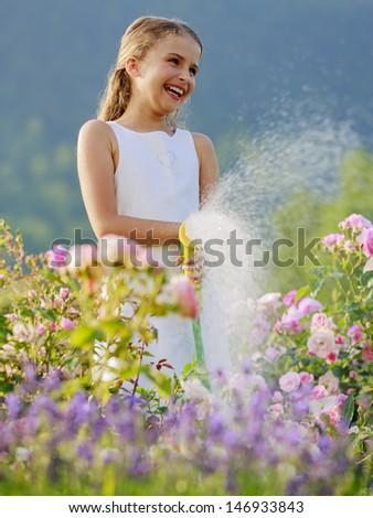 Summer fun,  garden, watering - beautiful  girl watering roses with garden hose - stock photo
