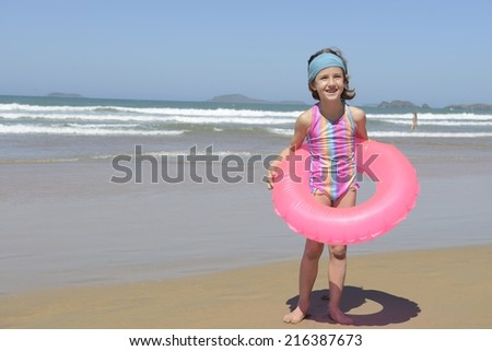 summer fun portrait: kid with inflatable swimming ring at the beach - stock photo