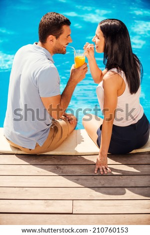 Summer fun. Top view of happy couple in casual wear sitting poolside together and drinking cocktail from one glass - stock photo