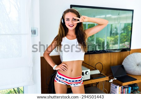 Summer funny portrait of young pretty dj woman, having fun in big light room, listening music in big headphones, fit sexy body, cute smile, long hairs, joy, student party. - stock photo