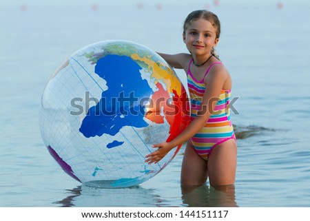 Summer game, young girl playing in the sea - stock photo