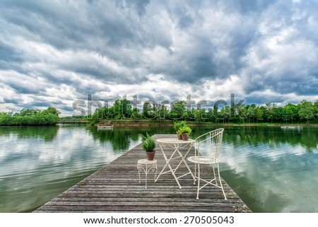 Summer garden with a small lake, stormy sky in the background  - stock photo